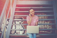 Girl with laptop talking phone Royalty Free Stock Images
