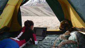 Girl with Laptop in the Tent. Girl with a laptop in a tent in the mountains stock footage