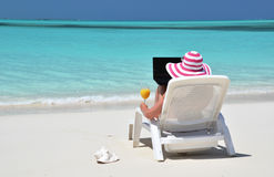 Girl with a laptop on the tropical beach Royalty Free Stock Photos