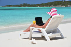 Girl with a laptop on the tropical beach Royalty Free Stock Photo