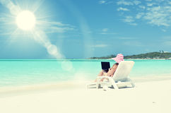 Girl with a laptop on the tropical beach Royalty Free Stock Image