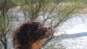 Girl with laptop working in the fresh air. A woman is typing on a laptop by the river. stock footage