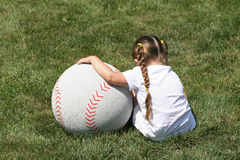 Girl and Large Baseball. A small young girl and a very large baseball royalty free stock images