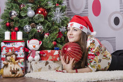 Girl with a large Christmas tree ball dreamily down right near the Christmas tree Royalty Free Stock Photography
