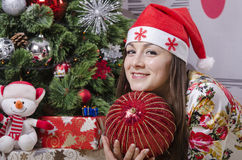 Girl with a large Christmas tree ball dreamily down right near the Christmas tree Stock Image