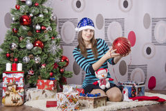 Girl with a large Christmas tree ball is sitting by the Christmas tree Stock Photography