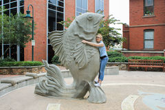 Girl with a Large Fish. Young teen girl hugging a large fish sculpture stock image