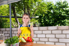Girl with Large Knife at Table with Vegetables Royalty Free Stock Image
