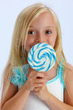 Girl with large lollipop. Cute young girl with large lollipop or sucker in front of face; studio background Stock Image