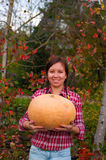 Girl with large pumpkin Royalty Free Stock Image