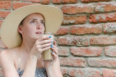 Girl with latte in hand and in a hat in cafe. Travel and Leisure Stock Photos