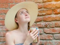 Girl with latte in hand and in a hat looking up. Travel and Leisure Royalty Free Stock Image