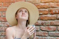 Girl with latte in hand and in a hat looking up. Travel and Leisure Royalty Free Stock Photography