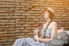 Girl with a latte in her hands and a hat pensively sits in a street cafe Royalty Free Stock Image