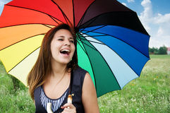 Girl laughing. Beautiful young girl with a colorful umbrella laughing outdoor Stock Photography