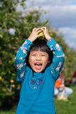 Girl Laughing and Balancing an Apple. Young girl laughing and trying to balance an apple on her head royalty free stock photography
