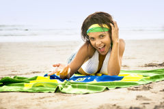 Girl laughing on beach with football and Brazil flag Royalty Free Stock Images