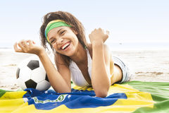 Girl laughing on beach with football and Brazil flag Stock Photo