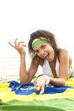 Girl laughing on beach with football and Brazil flag Royalty Free Stock Image