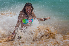 Girl laughing and crying in the spray of waves at Stock Images