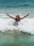Girl laughing and crying in the spray of waves at Royalty Free Stock Image