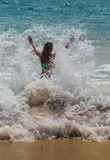 Girl laughing and crying in the spray of waves at Stock Image