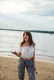 Girl laughing and holding phone on the beach Stock Photos