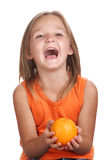 Girl laughing with orange. Happy laughing child holding a orange Royalty Free Stock Photography