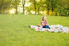 Girl on blanket at sunset Stock Images