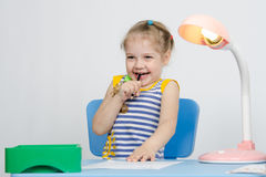 Girl laughing stuck a pencil in her mouth Royalty Free Stock Image