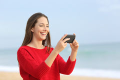 Girl laughing watching videos in smart phone Stock Photo