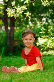 Girl laughs. The small beautiful girl sits on a green lawn and laughs Stock Images