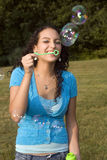 Girl laughs at blowing bubbles. An early twenties caucasian female playfully blows bubbles on a clear afternoon in a Connecticut, USA, meadow stock photo