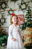Girl laughs cheerfully against the backdrop of New Year`s scenery. Child next to Christmas tree. The girl in white elegant dress Stock Image