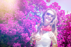 Girl laughs on the floral background in sunlight Stock Photography
