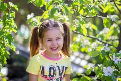 The girl laughs standing near the blossoming tree. At the dacha stock photos