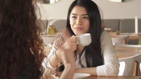 Girl laughs about what her friend telling at the cafe. Attractive brunette girl laughing about what her female friend telling at the cafe. Curly brown haired stock video