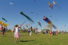 Girl launches a kite into the sky at the kite festival in the Park Tsaritsyno in Moscow stock photo