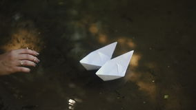 The girl launches two paper ships stock video