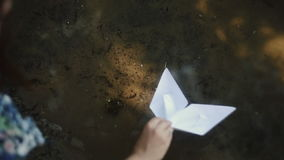 The girl launches two paper ships stock footage