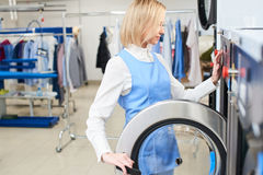 Girl Laundry worker selects a wash program. At the dry cleaners Stock Image