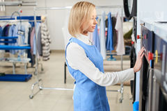 Girl Laundry worker selects a wash program. At the dry cleaners Royalty Free Stock Photo