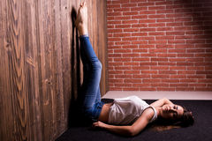 Girl lay against wooden and brick wall Royalty Free Stock Image