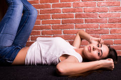 Girl lay against wooden and brick wall Stock Photo