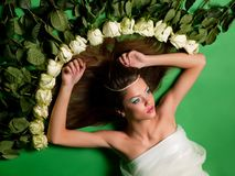 Girl lay among the flowers of roses Royalty Free Stock Image