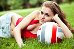 Girl lay on grass with volleyball ball Royalty Free Stock Photography