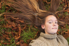 Girl laying on autumn ground with long hair scattered on the grass. Stock Photos