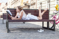 Girl laying on bench and reading book Stock Photo