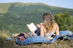 Girl laying on a blanket and reading a book on a picnic in the f Stock Photography