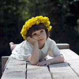 The girl laying on the bridge. In a wreath from dandelions Stock Photo